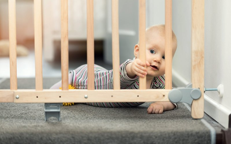 baby-holding-onto-wooden-baby-gate.jpg